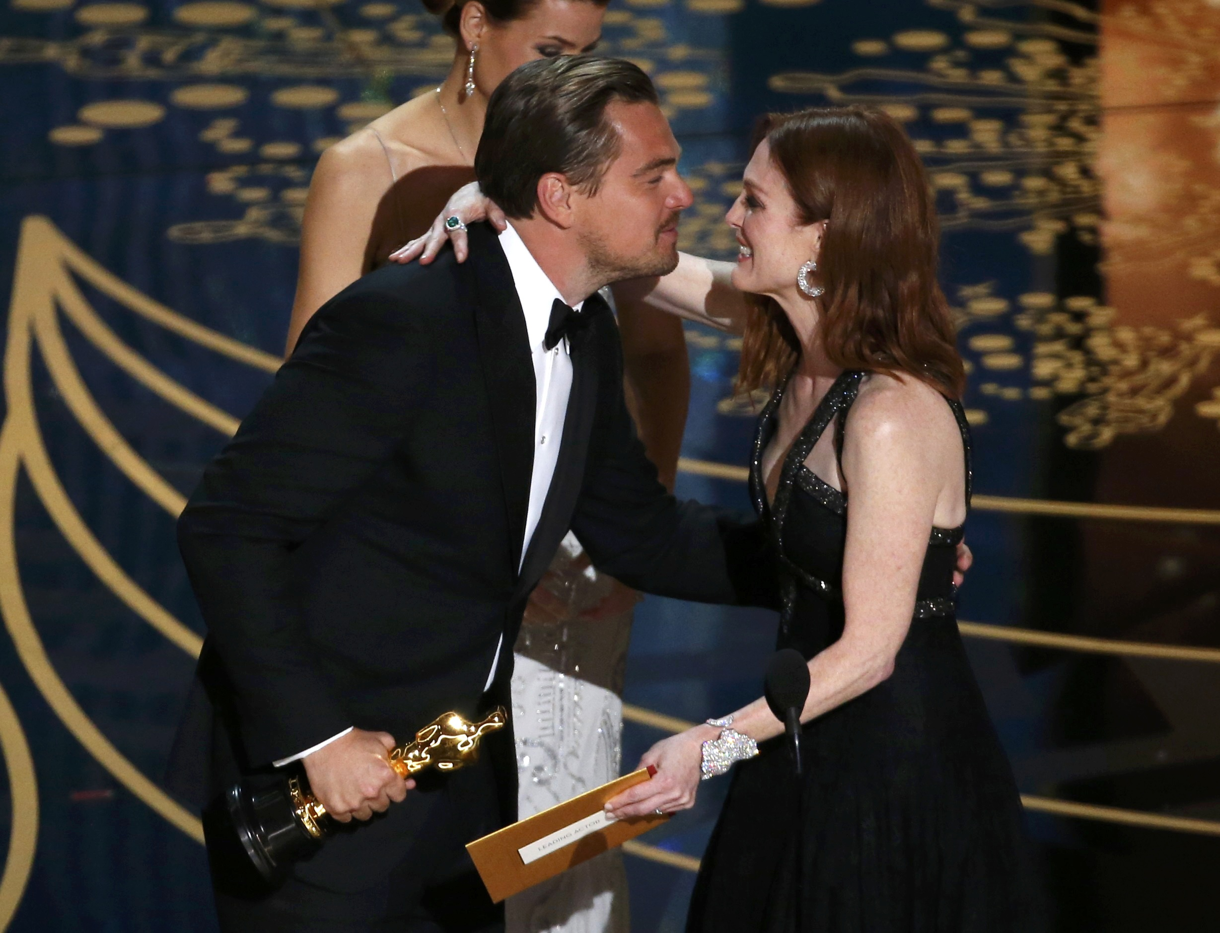 """Leonardo DiCaprio receives the Oscar for Best Actor for the movie """"The Revanant""""  from Julianne Moore at the 88th Academy Awards in Hollywood, California February 28, 2016.   REUTERS/Mario Anzuoni"""