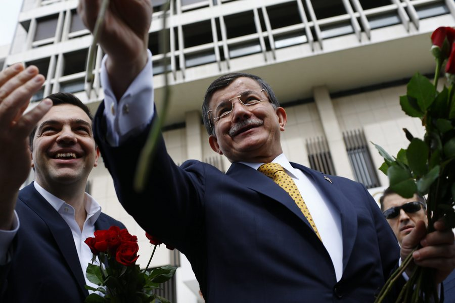 epa05200731 Greek Prime Minister Alexis Tsipras (L) and Turkish Prime Minister Ahmet Davutoglu (R) give flowers to female journalists before their meeting, in Izmir, Turkey, 08 March 2016. The UN refugee agency (UNHCR) slammed EU-Turkish plans to return migrants from Greece to Turkey, pointing out that such a move would violate European and international laws.  EPA/SEDAT SUNA