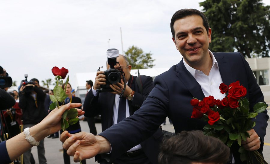 epa05200728 Greek Prime Minister Alexis Tsipras gives flowers to female journalists before meeting Turkish Prime Minister Ahmet Davutoglu (unseen), in Izmir, Turkey, 08 March 2016. The UN refugee agency (UNHCR) slammed EU-Turkish plans to return migrants from Greece to Turkey, pointing out that such a move would violate European and international laws.  EPA/SEDAT SUNA